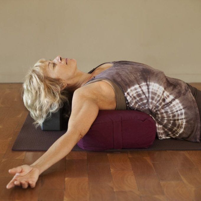 Middle age woman resting on a yoga bolster.